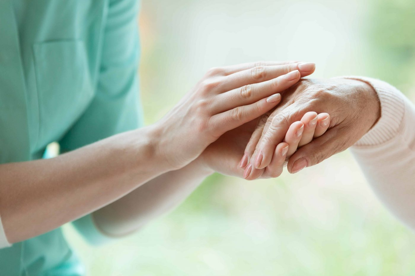 Young caretaker massaging pensioner's hand with Parkinson's disease