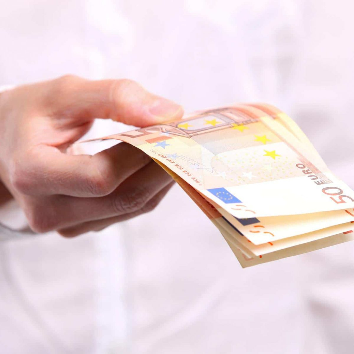 Female hand holding fifty euro banknotes