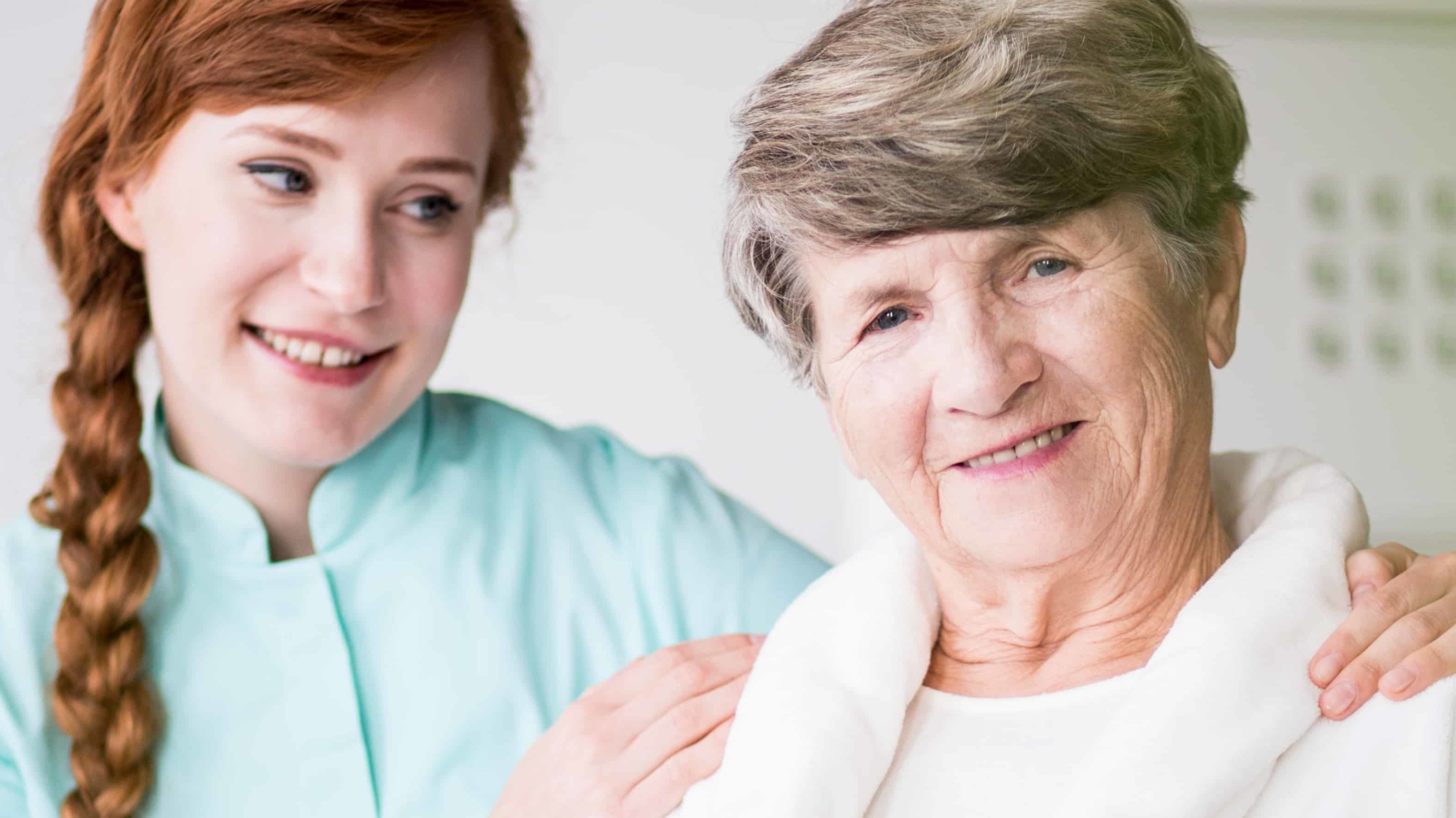 Young nurse and smiling elderly patient in hospital