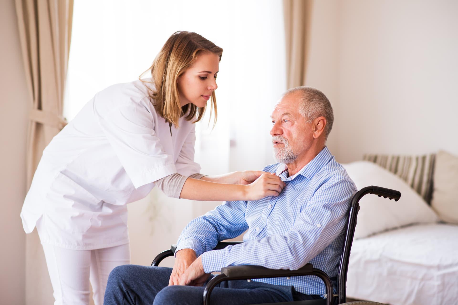 - nurse and senior man in wheelchair during home PFZFAHV - Verhinderungspflege