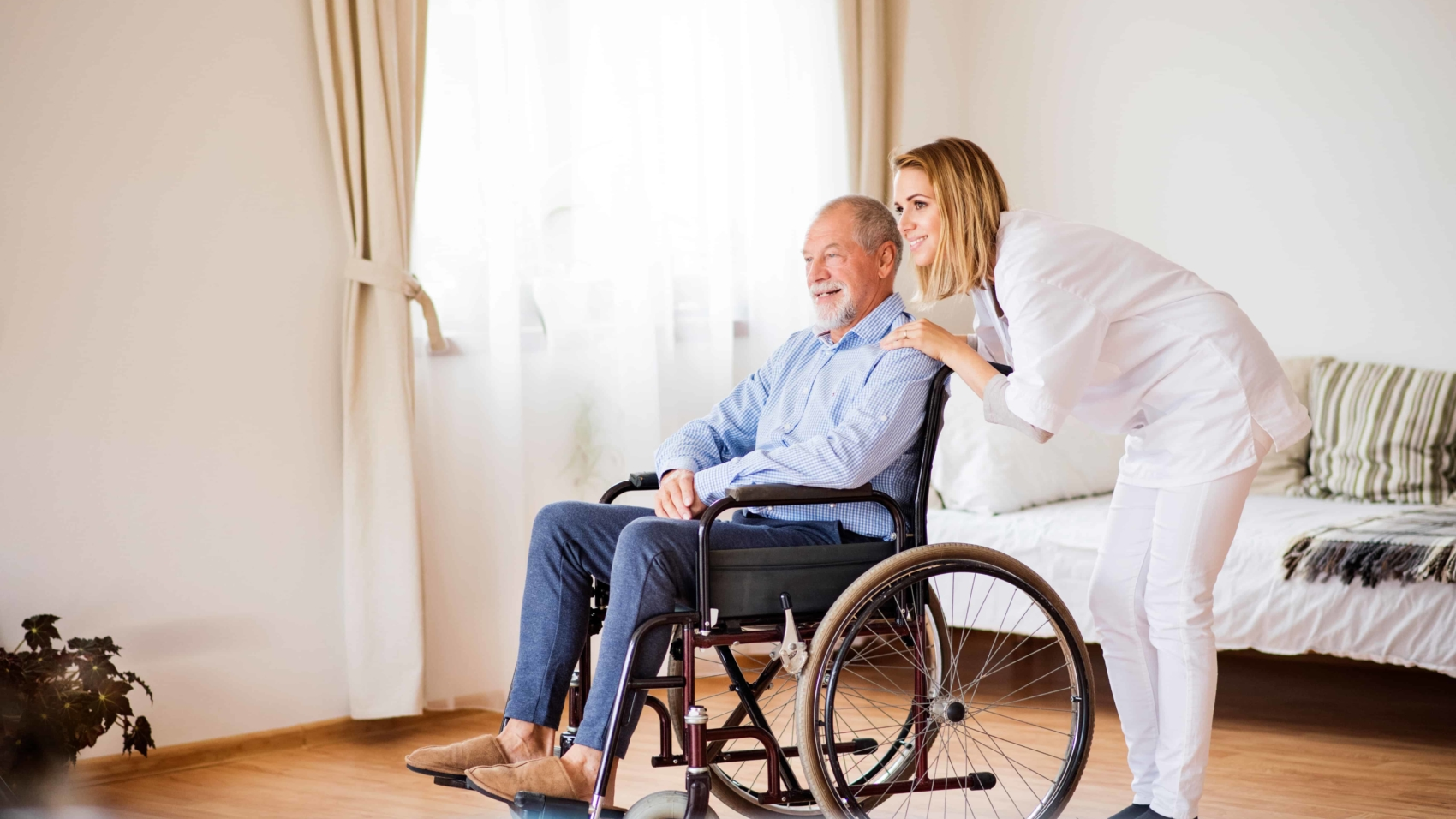 Health visitor or a nurse and a senior man in a wheelchair during home visit. Man and woman looking out of a window.